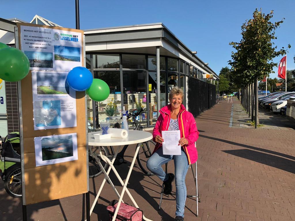 Annemarie Kooiman met een Behoud-Het-IJsselmeer-stand bij Winkelcentrum Beldershof in Andijk