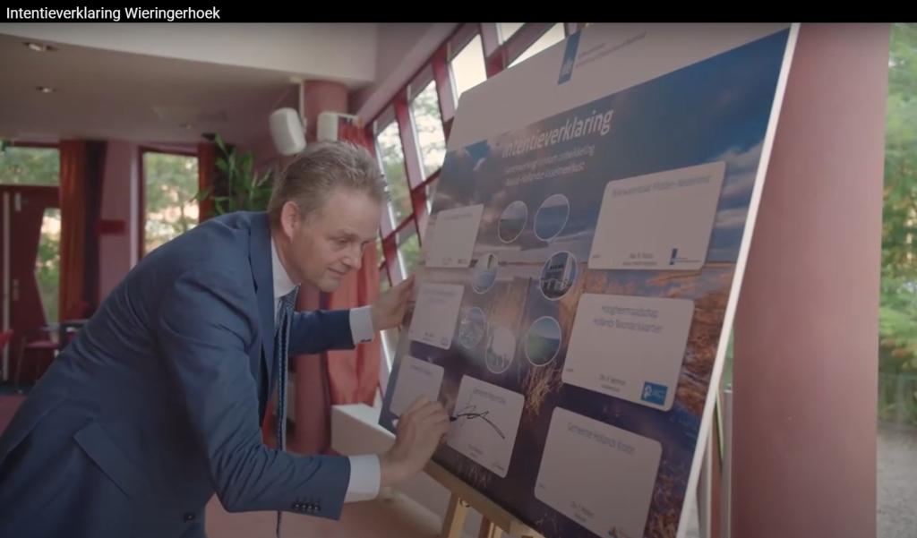 """Wethouder Harry Nederpelt (CDA) zet zijn handtekening onder de intentieverklaring (Beeld YouTube) - Petitie """"Behoud Het IJsselmeer!"""" overhandigd aan Rijkswaterstaat"""